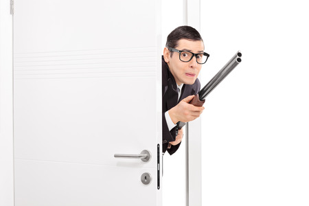 gun room: Terrified man with rifle entering a room isolated on white background
