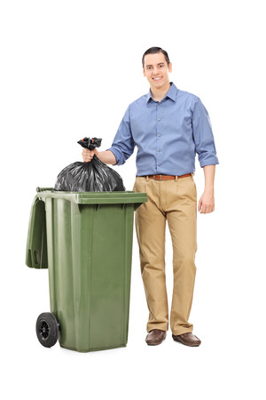 Full length portrait of a man throwing out garbage isolated on white background