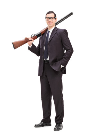 Full length portrait of a businessman holding a rifle over his shoulder isolated on white background photo