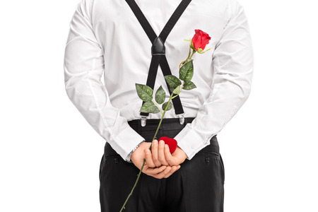 gift behind back: Close-up on a man holding flower and a red box behind his back isolated on white background