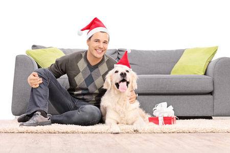 labrador christmas: Man and a dog with Santa hats sitting by a sofa isolated on white background