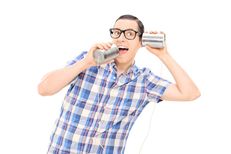 tin can phone: Silly man talking to himself through tin can phone isolated on white background