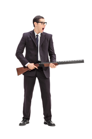 Full length portrait of an angry man holding a rifle and shouting isolated on white background photo