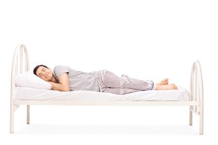 Gelukkig jonge man slapen in een bed op een witte achtergrond