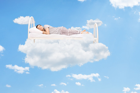 cloud: Man sleeping on a bed in the clouds high up in the sky