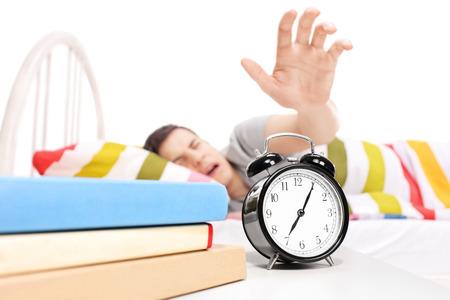 sleepy man: Sleepy man reaching for the alarm clock isolated on white background