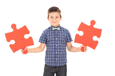two pieces: Kid holding two pieces of a puzzle isolated on white background