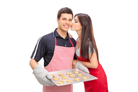 kiss biscuits: Young couple baking cookies together isolated on white background