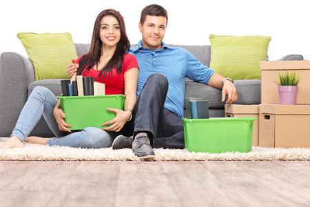 stuff: Young couple sitting on the floor with moving boxes full of their stuff isolated on white background