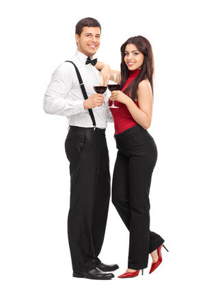 Full length portrait of a young couple drinking red wine and posing isolated on white background photo