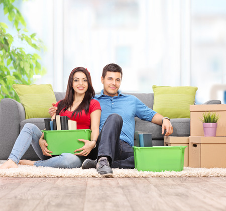 stuff: Young couple sitting on the floor with moving boxes full of their stuff at home shot with tilt and shift lens