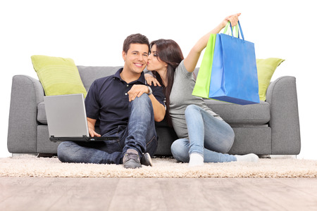 Woman with shopping bags kissing her boyfriend seated by a sofa isolated on white background photo