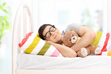 Childish young man sleeping with a teddy bear at home Reklamní fotografie