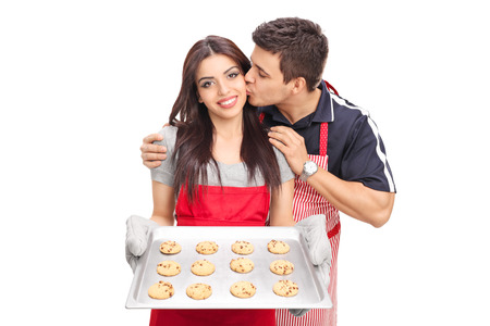 kiss biscuits: Woman baking cookies with her boyfriend isolated on white background