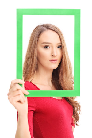 Beautiful woman posing and holding a green picture frame in front of her face isolated on white background photo