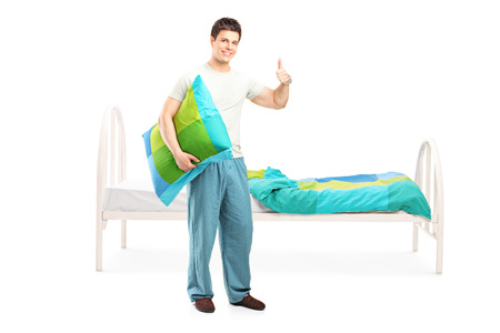 posing  agree: Full length portrait of a man in pajamas giving thumb up and standing by his bed isolated on white background Stock Photo