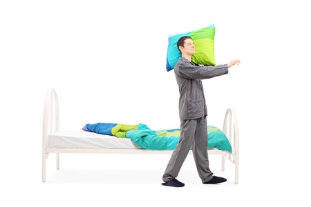 Full length portrait of a young man in pajamas sleepwalking by his bed isolated on white background Stock Photo