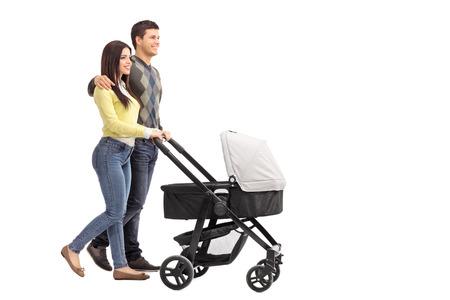 Volledige lengte portret van een jonge ouders duwen van een kinderwagen op een witte achtergrond
