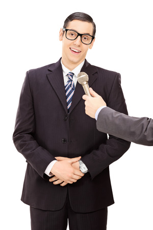 smug: Vertical shot of a young businessman being interviewed isolated on white background Stock Photo
