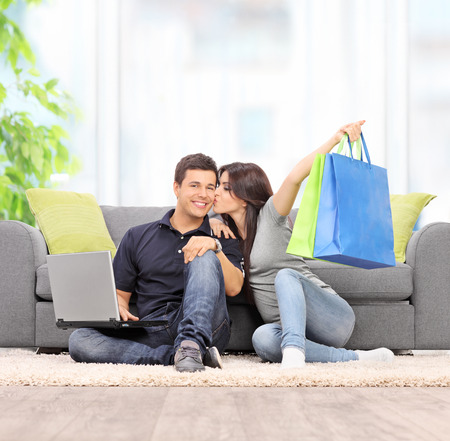 Woman with shopping bags kissing her boyfriend seated by a sofa at home shot with tilt and shift lens photo