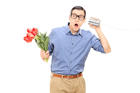 Young man holding flowers and listening through a tin can phone isolated on white background photo