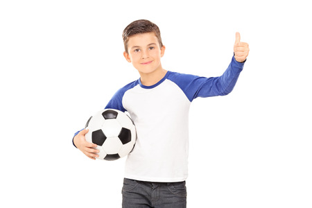 posing  agree: Boy holding a football and giving a thumb up isolated on white background