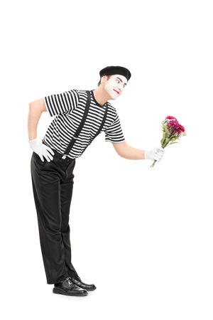 mimo: Retrato de cuerpo entero de un mimo de regalar flores a alguien aislado en fondo blanco