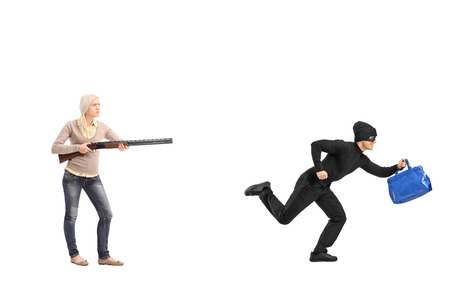 Full length portrait of an angry woman chasing a burglar with a shotgun isolated on white background photo