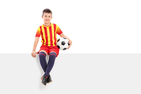 junior soccer: Junior soccer player sitting on a signboard isolated on white background Stock Photo