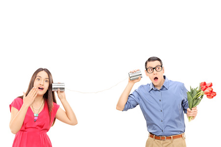 Man and a woman talking through a tin can phone isolated on white background photo