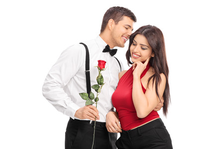 love expression: Romantic guy whispering something to a girl and holding a red rose isolated on white background