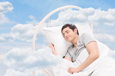 Joyful man sleeping on a bed in the clouds