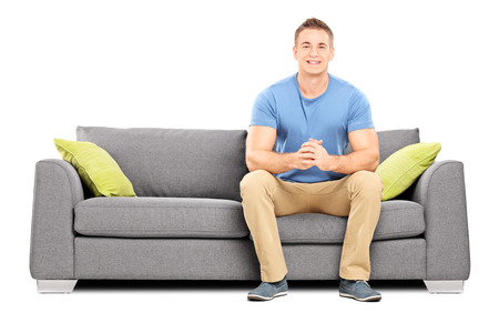 sit studio: Handsome young man sitting on a modern sofa isolated on white background