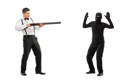outraged: Angry man threatening a burglar with rifle isolated on white background