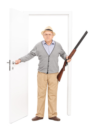 old rifle: Full length portrait of an angry senior holding a shotgun and walking through a door isolated on white background