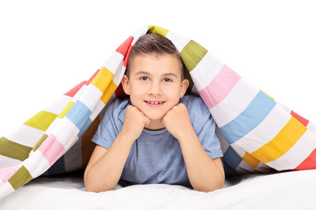 one little boy: Little boy lying on bed covered with a blanket isolated on white background Stock Photo