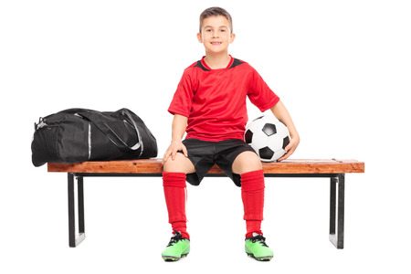 junior soccer: Junior soccer player sitting on a bench and holding a football isolated on white background