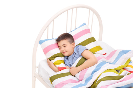 Cute little boy sleeping in a comfortable bed isolated on white background photo