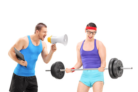 nerdy: Fitness coach motivating a nerdy guy via megaphone isolated on white background