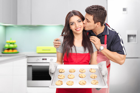 Young couple baking cookies in the kitchen at home photo