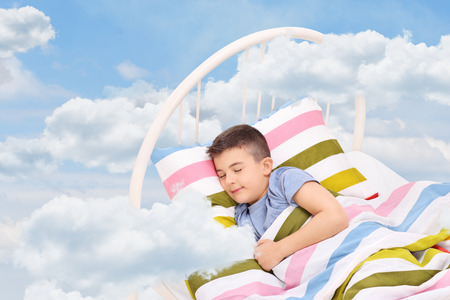 Cute little boy sleeping on a bed in the clouds photo