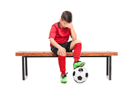 Sad kid in soccer uniform sitting on a bench isolated on white background