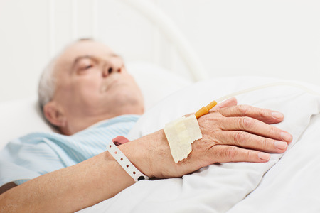 1 mature man: Sick senior lying in a hospital bed with iv drip attached on his hand with the focus on the iv set isolated on white background