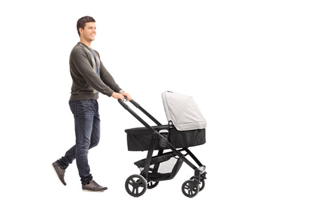 Full length portrait of a young father pushing a baby stroller isolated on white background
