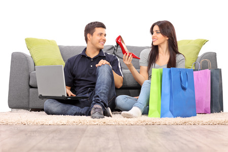 clothes shopping: Woman showing her new shoes to her boyfriend isolated on white background