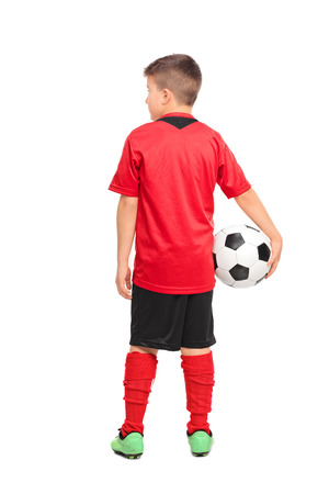 child ball: Full length portrait of a junior soccer player holding a ball isolated on white background, rear view
