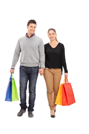 people walking white background: Full length portrait of a young couple walking with shopping bags isolated on white background