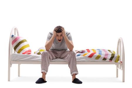 hombre sentado: Hombre joven que sufre de insomnio aislado en fondo blanco Foto de archivo