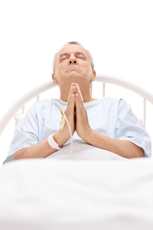 incurable: Senior patient praying in a hospital bed with an iv drip attached to his hand