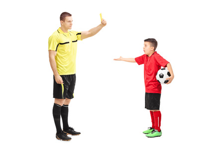 junior soccer: Football referee showing yellow card to a junior soccer player isolated on white background